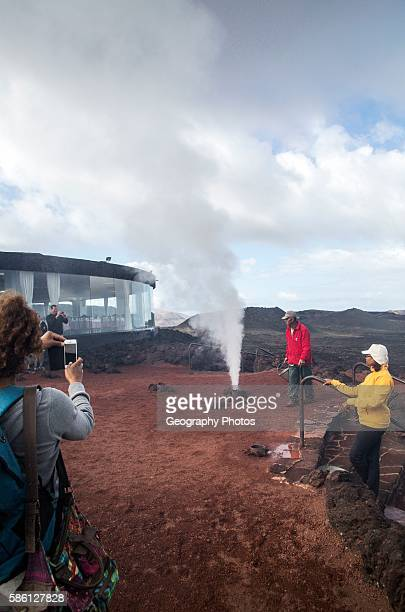 Tourists watch steam rise from geyser spout Parque Nacional de Timanfaya national park Lanzarote Canary Islands Spain