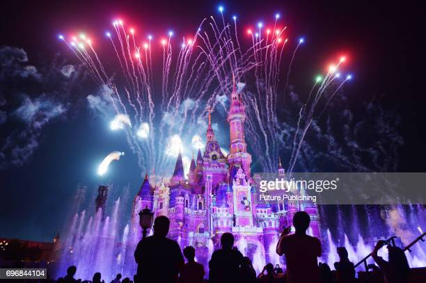Tourists watch the celebration show marking the first anniversary of the Shanghai Disney Resort at the 1968foot Enchanted Storybook Castle on June 16...