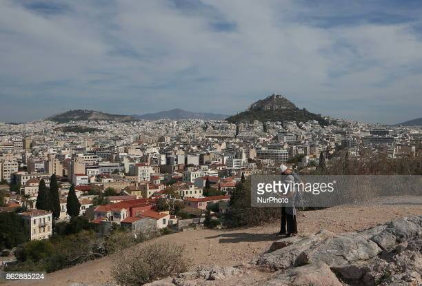 Tourists watch the map on the Areopagus rock in Athens Greece Wednesday October 18 2017