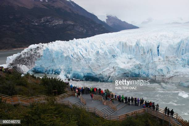 Tourists watch the Perito Moreno Glacier, at Los Glaciares National Park, near El Calafate in the Argentine province of Santa Cruz, on March 10,...