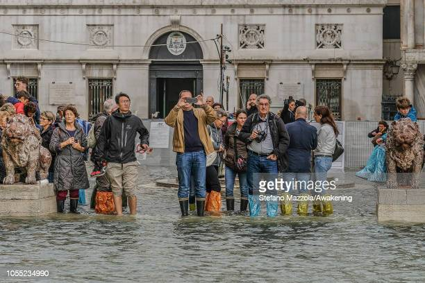 Tourists watch the Piazza San Marco filling with water on October 29 2018 in Venice Italy Due to the exceptional level of the acqua alta or High Tide...