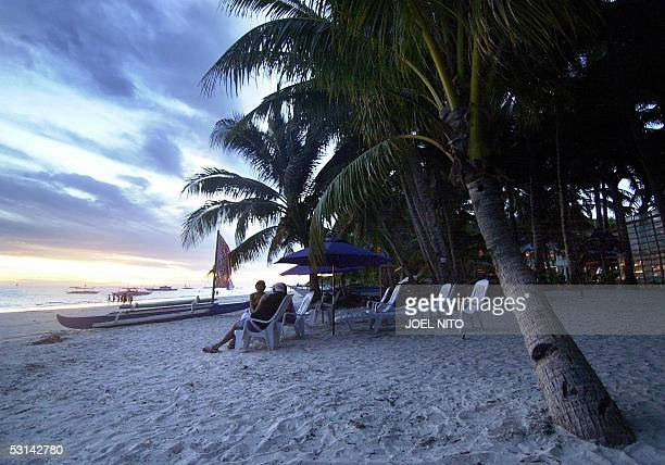 STORY PHILIPPINESTOURISMLANDBORACAY Tourists watch the sun go down on the famous white beach of the central Philippine island of Boracay 11 June 2005...
