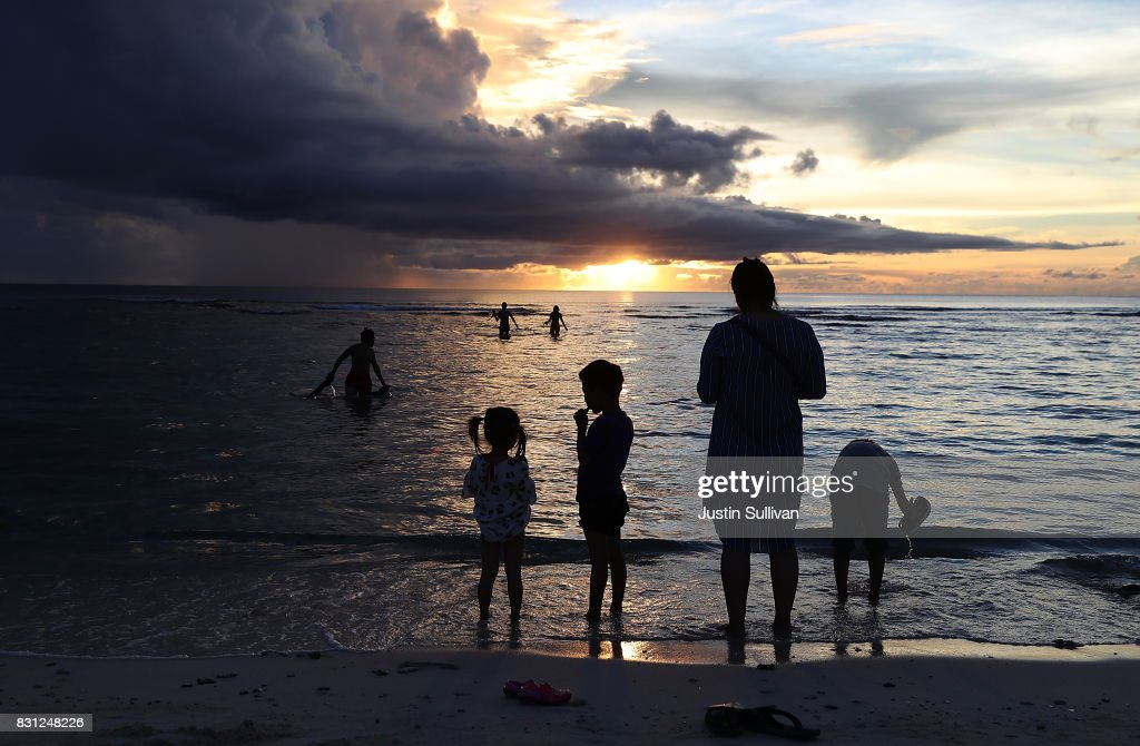 Tourists watch the sunset from Gun Beach on August 14, 2017 in Tamuning, Guam. The American territory of Guam remains on high alert as a showdown between the U.S. and North Korea continues. North Korea has said that it is planning to launch four missiles near Guam by the middle of August. Guam is home to around 7,000 American troops and 160,000 residents.