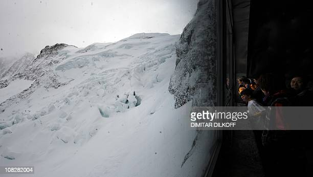 Tourists watch through a window of the Eiger tunnel on the way to the highest railway station in Europe the Jungfraujoch and called the Top of Europe...