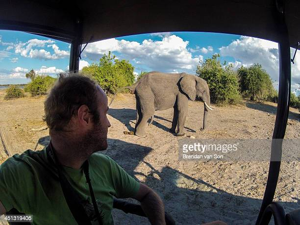 CONTENT] A tourists watches an elephant while on safari in Chobe National Park Botswana