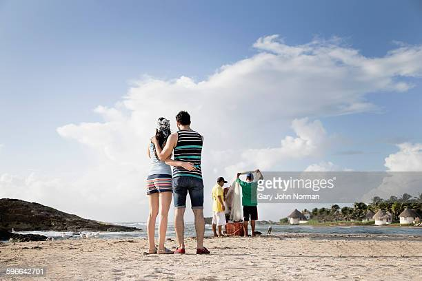 Tourists watching fishermen on beach