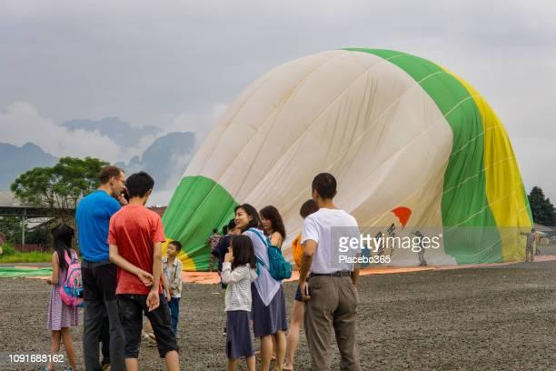 Tourists watching Hot air balloon landing, Vang Vieng, Laos