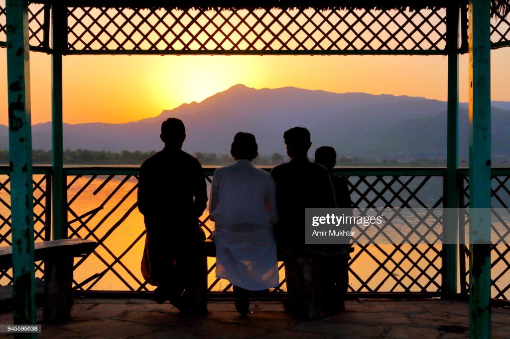 Tourists watching sunset at lake : Stock Photo