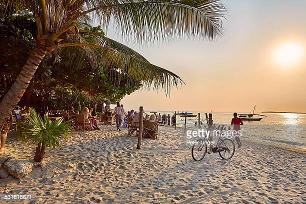 tourists watching sunset  at restaurant on beach - zanzibar island stock photos and pictures