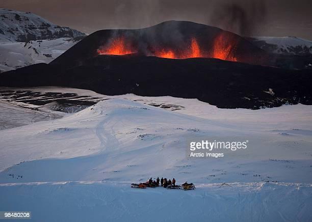 tourists watching the lava fountains - fimmvorduhals volcano stockfoto's en -beelden