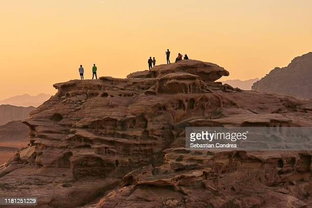 tourists watching the sunset from the highest hill, in a quiet and miraculous way, wadi rum, jordan. - jordanian stock pictures, royalty-free photos & images