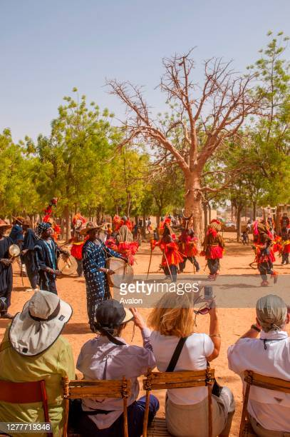 Tourists watching the traditional dances of the Dogon people in the village of Sangha in the Dogon country in Mali, West Africa.