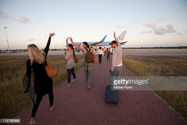 Tourists wave goodbye before embarking on the flight home at Kralendijk Flamingo Airport on February 11, 2011 on the island of Bonaire. Bonaire has...