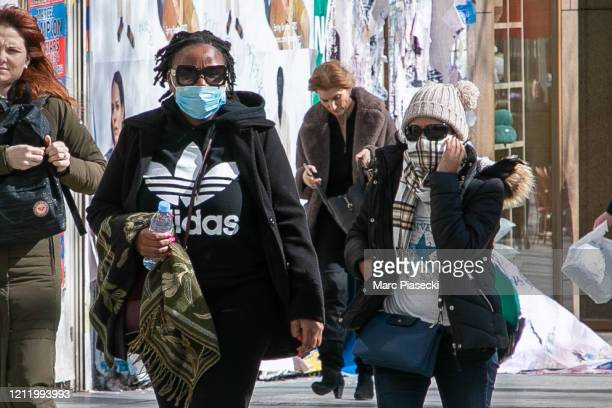 Tourists wear a protective facemask as they stroll on the Avenue des ChampsElysees during a world COVID19 outbreak in Paris on March 12 2020 in Paris...