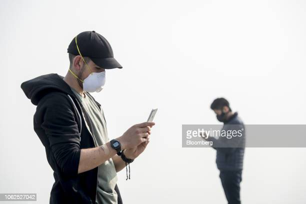 Tourists wear face masks as smoke from the Camp Fire fills the air in San Francisco California US on Friday Nov 16 2018 The Camp Fire burning about...