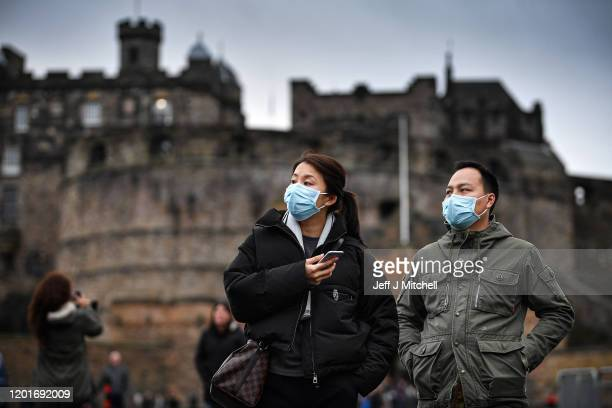 Tourists wear face masks as they visit Edinburgh Castle on January 24 2020 in Edinburgh Scotland It has been confirmed that 14 people in Scotland...