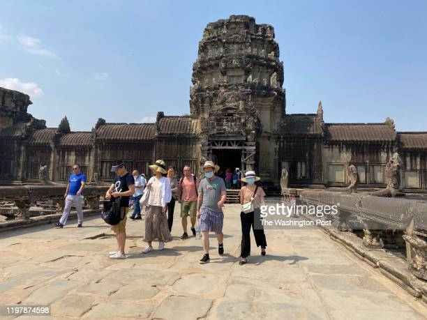 Tourists wear face masks while visiting the Angkor Wat temple in Cambodia on January 29, 2020.