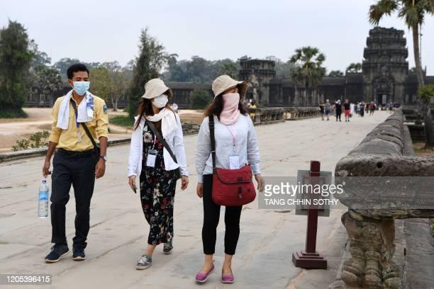 Tourists wear facemasks, amid concerns about the spread of the COVID-19 novel coronavirus, during their visit the Angkor Wat temple in Siem Reap...