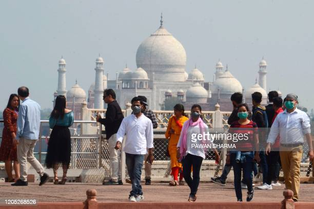 Tourists wear facemasks as a preventive measure against the spread of the COVID-19 coronavirus outbreak, near Taj Mahal in Agra on March 5, 2020. -...