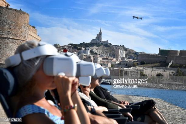 TOPSHOT Tourists wear immersive video headset as they take part in virtual flight tour of Marseille's VieuxPort via a drone piloted by a professional...