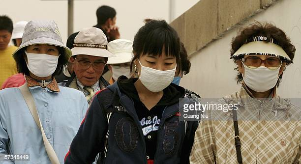 Tourists wear masks to prevent dust as they visit Tiananmen Square on April 17 2006 in Beijing China Millions of residents woke up to find their city...