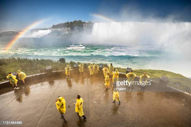 tourists wear ponchos to protect from the wet mist in niagara falls ontario canada - poncho stock pictures, royalty-free photos & images