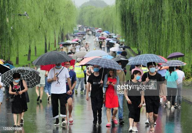 Tourists wearing face masks and holding umbrellas visit Baidi at West Lake in rain on the last day of three-day Dragon Boat Festival holiday on June...