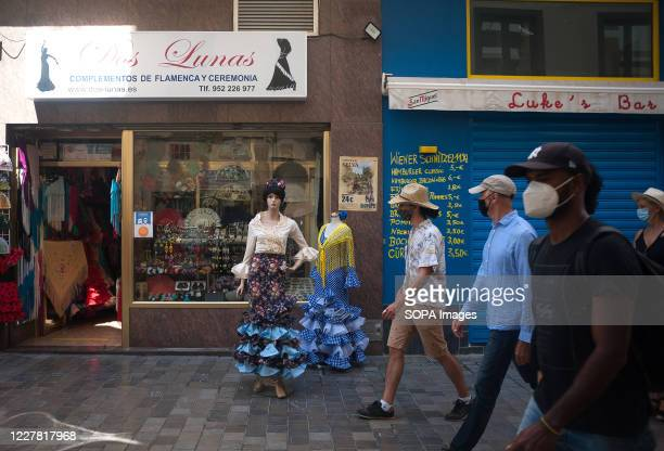 Tourists wearing face masks as a precaution, walking past a flamenco shop in downtown city. The government of UK has imposed a quarantine to all...