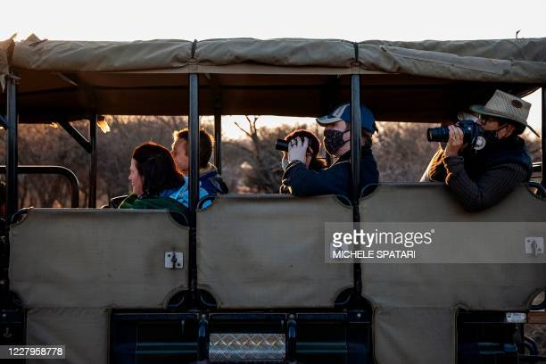 Tourists wearing face masks as a preventive measure against the spread of COVID19 coronavirus look at a lioness during a guided safari tour at the...