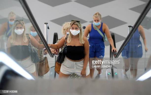 Tourists wearing face masks use an escalator at Split International Airport in Split, Croatia, on August 21, 2020. - As United Kingdom removed...