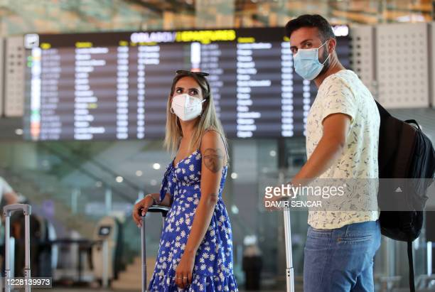 Tourists wearing face masks wait at Split International Airport in Split, Croatia, on August 21, 2020. - As United Kingdom removed Croatia from the...