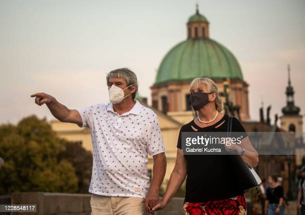 Tourists wearing face masks walk at sunset on medieval Charles Bridge on September 16 in Prague, Czech Republic. The Czech Republic records the...