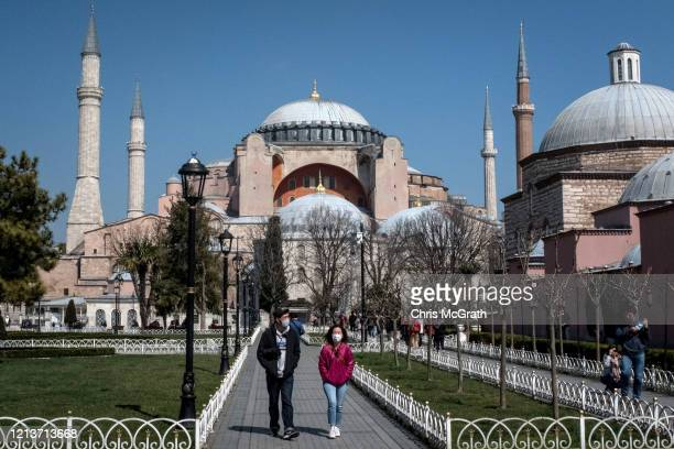 Tourists wearing face masks walk in front of Istanbul's famous Hagia Sophia on March 20, 2020 in Istanbul, Turkey. Turkey has confirmed four deaths...