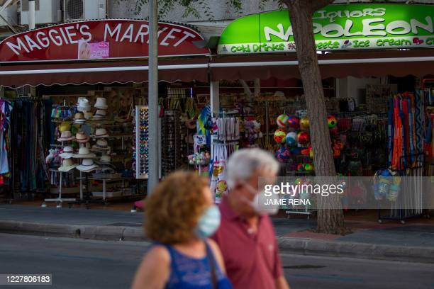 Tourists wearing face masks walk past shops in Palmanova on the Island of Mallorca on July 27 2020 Tour operator TUI has cancelled all British...
