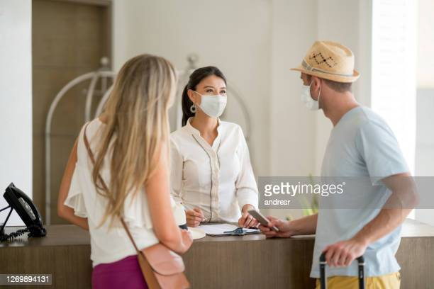 turistas usando máscaras faciais enquanto fazem o check-in no hotel - hotel - fotografias e filmes do acervo
