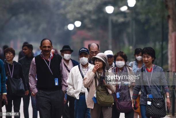 Tourists wearing masks as they leave Raj Ghat on a cold and smoggy day on December 3 2017 in New Delhi India Delhi witnessed a sharp drop in...