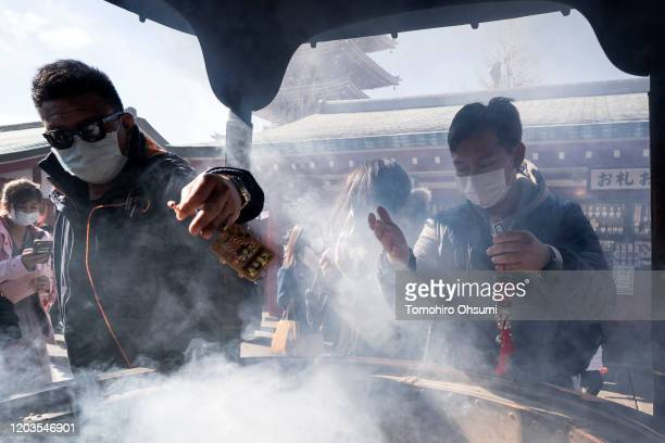 Tourists wearing masks gather around an incense burner to wave smoke towards themselves at a temple in the Asakusa district on February 02, 2020 in...