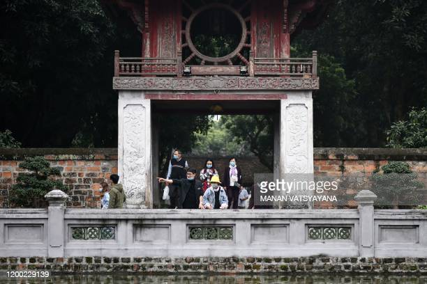 Tourists wearing protective facemasks amid concerns of the COVID-19 coronavirus outbreak visit the Temple of Literature in Hanoi on February 12, 2020.
