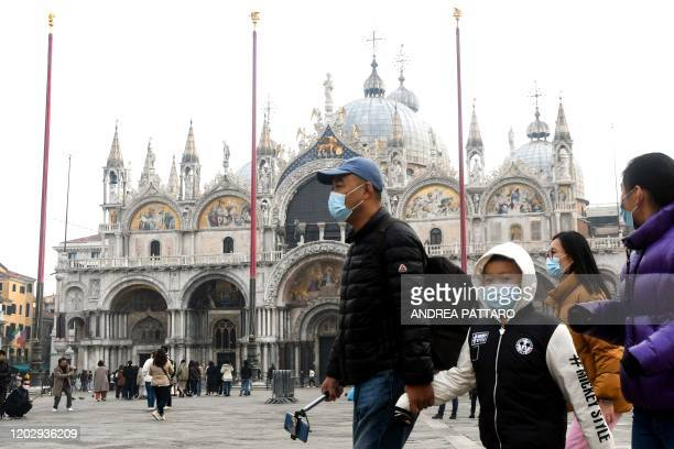 Tourists wearing protective facemasks visit the Piazza San Marco in Venice on February 24 2020 during the usual period of the Carnival festivities...
