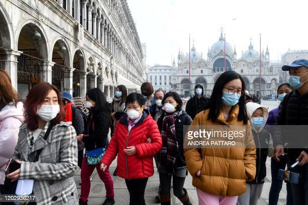 TOPSHOT Tourists wearing protective facemasks visit the Piazza San Marco in Venice on February 24 2020 during the usual period of the Carnival...