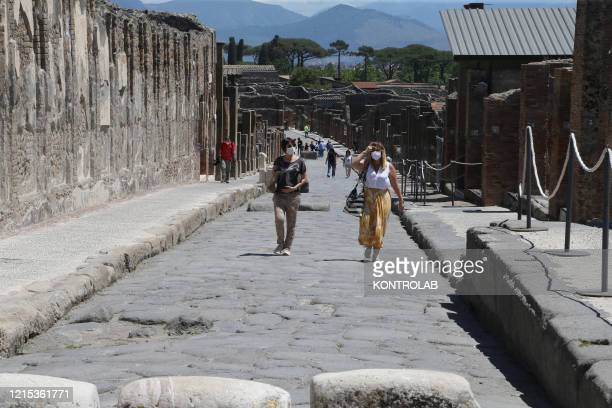 Tourists wearing protective mask visit the reopened archaeological site of Pompeii, the ancient Roman town buried by the eruption of the Vesuvius...