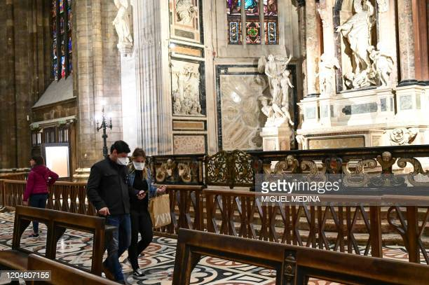 Tourists wearing protective masks as a protection against the Coronavirus visit the Milan Cathedral on March 2 2020 The Duomo reopens for the first...