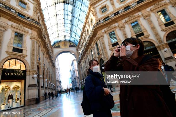 Tourists wearing protective masks take pictures in Galleria Vittorio Emanuele II in the centre of Milan on February 28 after COVID19 the novel...