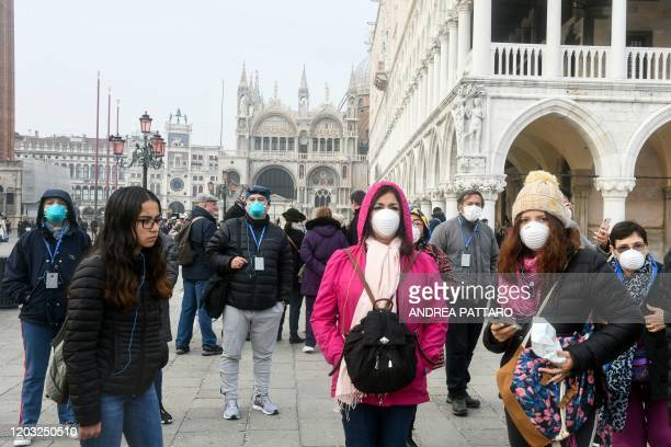 Tourists wearing protective masks visit Venice on February 25 during the usual period of the Carnival festivities which have been cancelled following...
