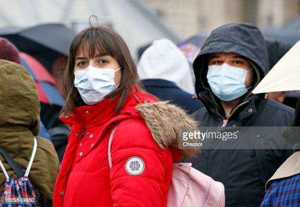 Tourists wearing protective masks walk past the Louvre Museum as the museum was closed for a staff meeting about the coronavirus outbreak on March 2...