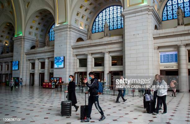 Tourists wearing protective masks walk through the main entrance at Union Station in Washington DC on March 9 2020 US health authorities urged...