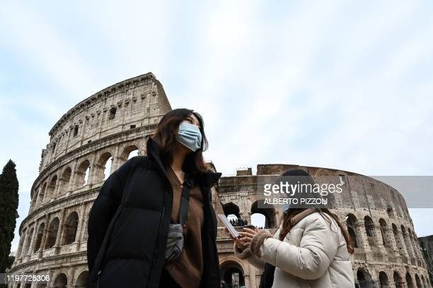 TOPSHOT Tourists wearing protective respiratory masks tour outside the Colosseo monument in downtown Rome on January 31 2020 The Italian government...