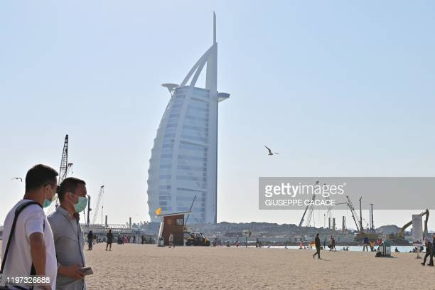 Tourists wearing surgical masks are pictured on a beach next to Burj Al Arab in Dubai on January 29 2020 The United Arab Emirates announced the first...