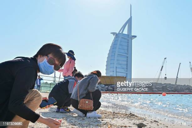 Tourists wearing surgical masks search for seashells on a beach next to Burj Al Arab in Dubai on January 29 2020 The United Arab Emirates announced...