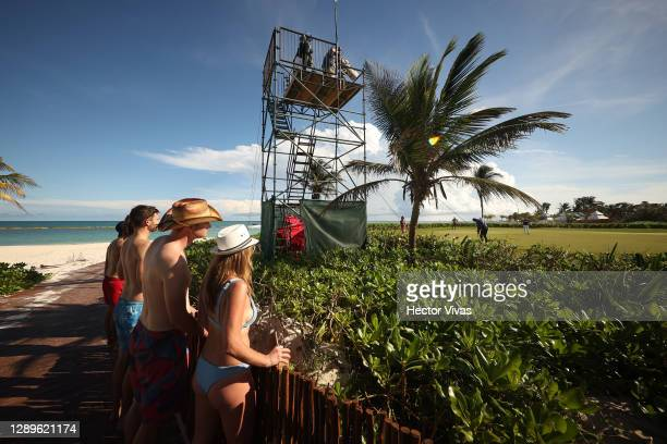 Tourists wearing swimsuits look at Akshay Bhatia of the United States putts on the 15th green during the third round of the Mayakoba Golf Classic at...